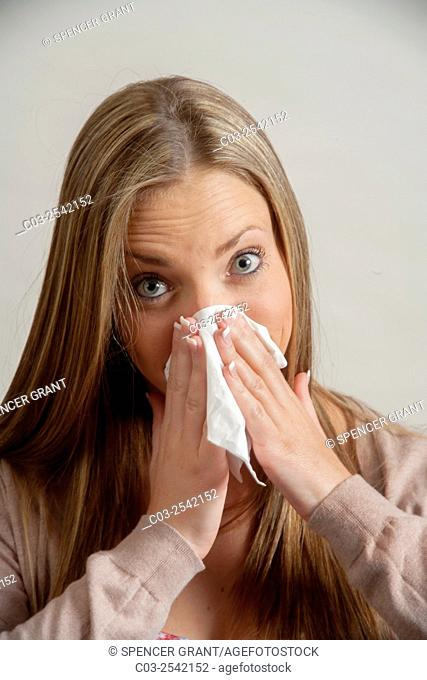 Using a handkerchief, a young adult woman blows her nose in Laguna Beach, CA. Note Cardigan sweater