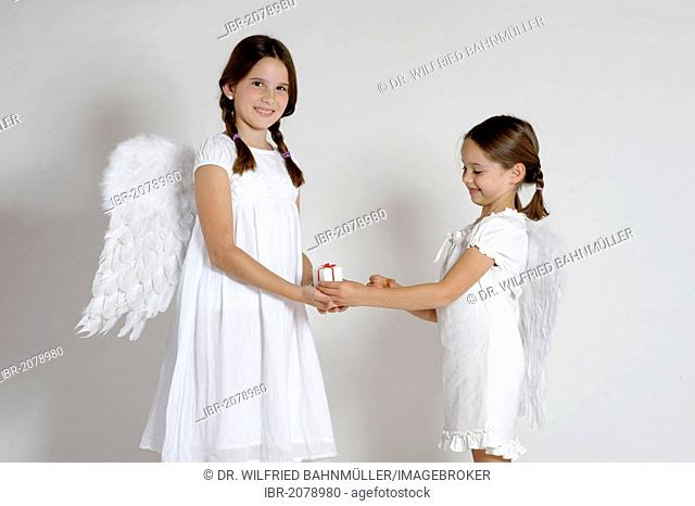 Two girls dressed up as Christmas angels, with a gift, Christmas