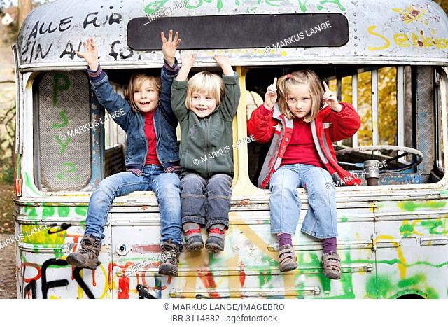 Three children sitting in a disused bus