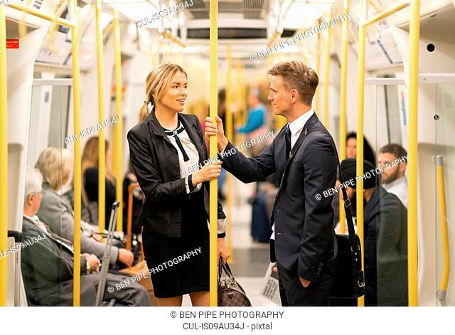 Businessman and businesswoman talking in tube, London Underground, UK