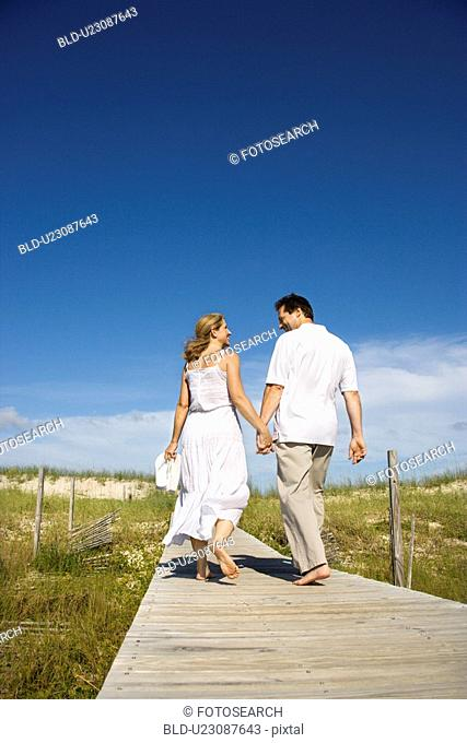 Couple holding hands walking down beach access path