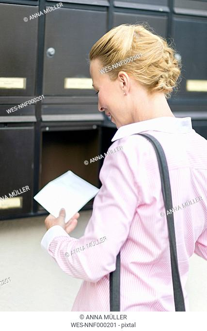 Woman standing in front of mailbox watching letter