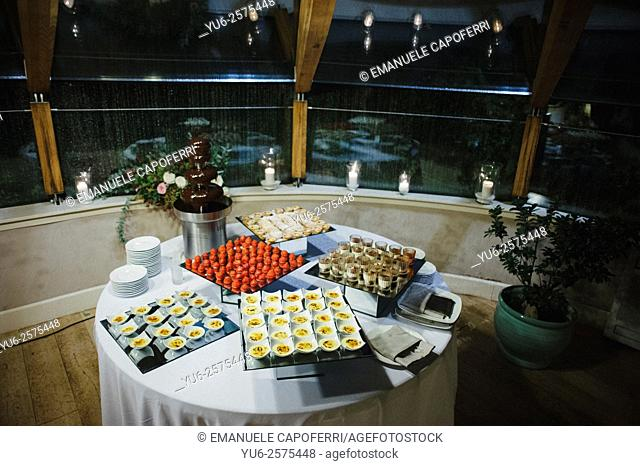 Displayware with sweets on the table on the veranda, at night