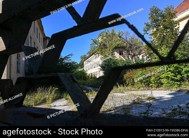 09 September 2021, Berlin: View through a former entrance gate to unused, dilapidated property. The site was cleared of Soviet troops in 1990