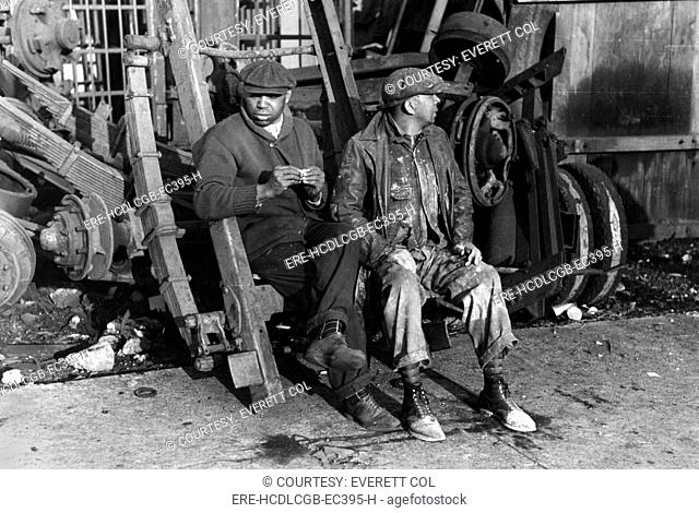 Men sitting on parts of truck in junkyard, South Side of Chicago, Illinois, photograph by Lee Russell, April, 1941