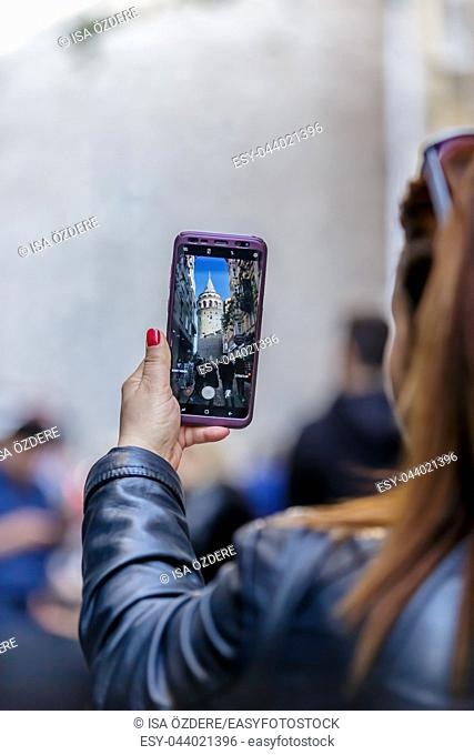 Unidentified woman takes picture of Galata Tower, a medieval famous landmark stone tower architecture, in Beyoglu, Istanbul. 29 April 2018