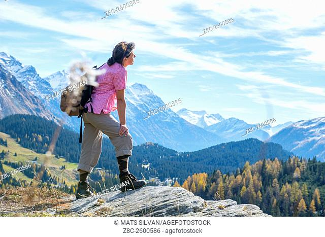 Woman with back pack enjoy panoramic view over snow-capped mountain in a sunny summer day in Grisons, Switzerland