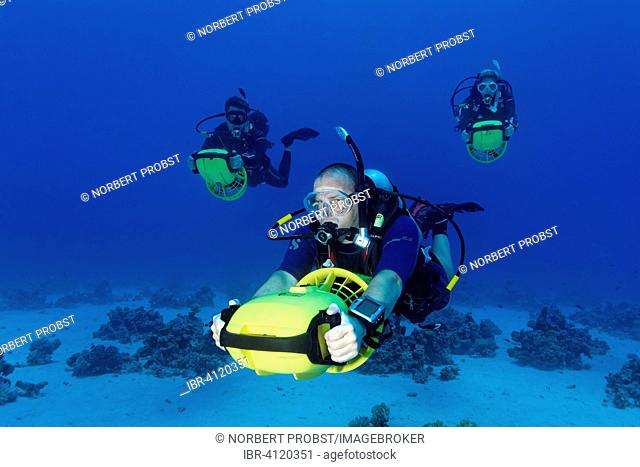 Divers with diver propulsion vehicles exploring a coral reef, Soma Bay, Hurghada, Egypt, Red Sea