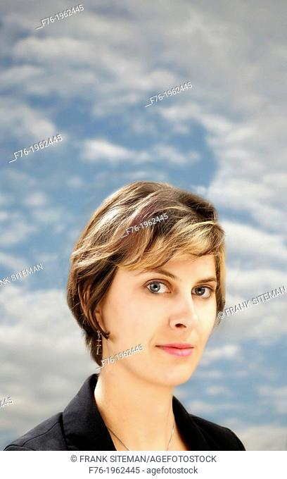 Portrait of young woman with clouds in background