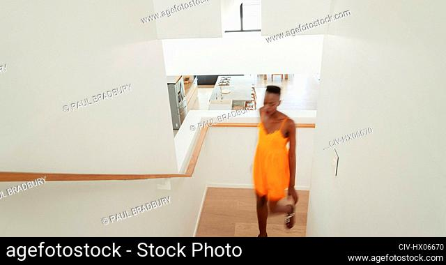 Young woman walking up staircase