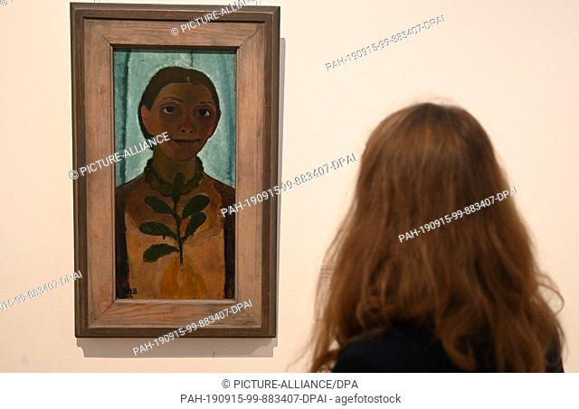 "12 September 2019, Bremen: An employee of the Paula Modersohn-Becker Museum looks at Paula Modersohn-Becker's painting """"Self-Portrait with Camellia Branch"""""