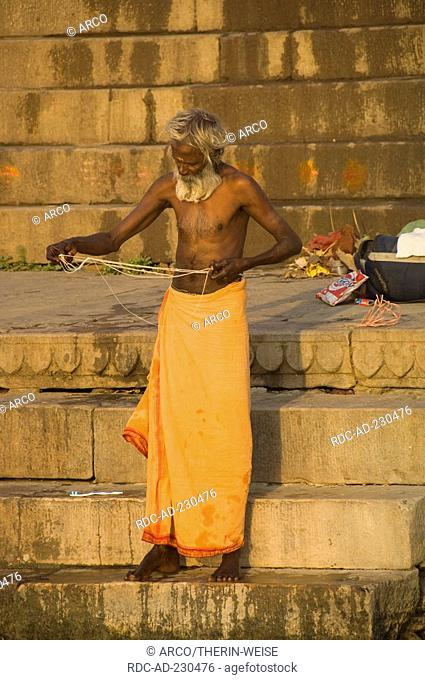 Indian man preparing for traditional ablution in river ganges, ghats, Varanasi, Benares, Uttar Pradesh, India