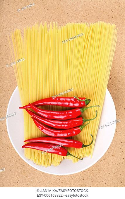 Plate with fresh chili peppers and dried uncooked pasta, over wooden background