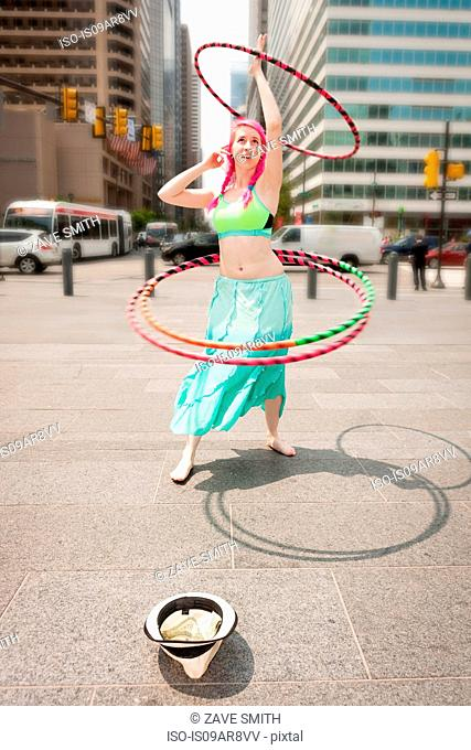 Young female performer hoola hooping on city street, Philadelphia, Pennsylvania, USA