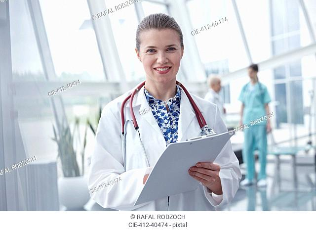 Portrait smiling, confident female doctor with clipboard in hospital