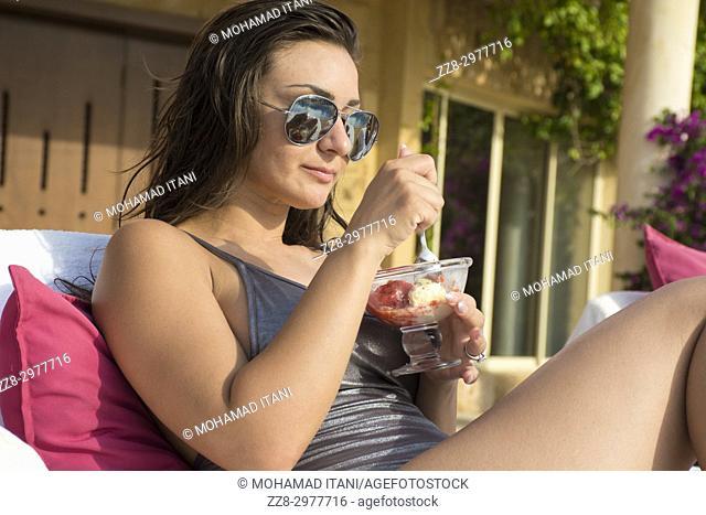 Beautiful woman wearing bikini and sunglasses eating icecream while sunbathing by the pool