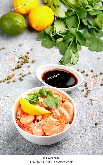 Shrimps prawns with lemon, cilantro and soy sauce in a white plate