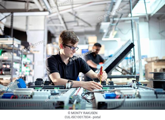 Apprentice electronics engineers in electronics assembly factory