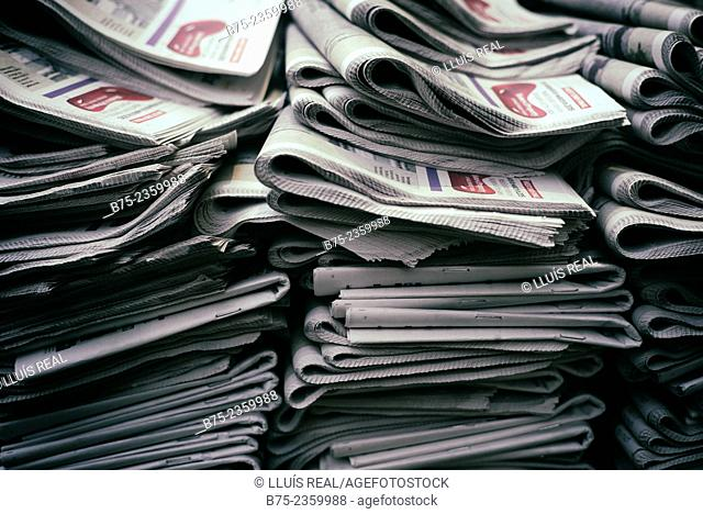 Closeup of a pile of folded complimentary newspapers in the street. London, England, UK, Europe