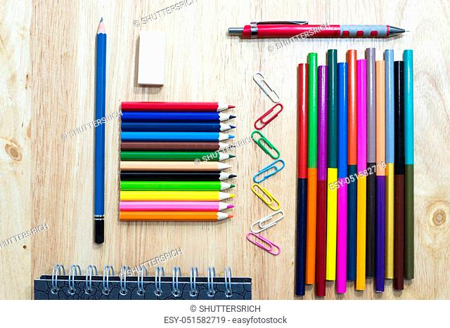 Colorfully Office and art stationery objects on wood table with a notebook