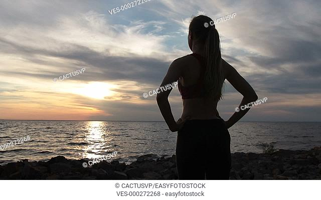 Young slim lady in sports clothes enjoying sunset