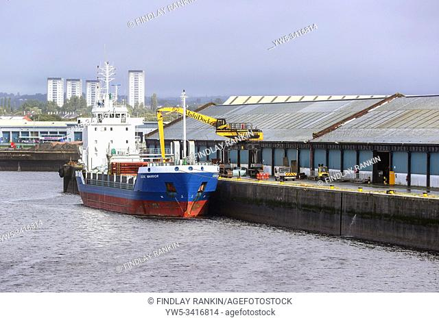 Cargo ship being unloaded at a pier at King George V docks, Glasgow, Scotland, UK