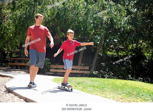 Boy with father practicing on skateboard in park