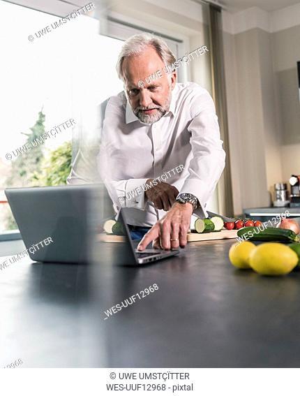 Mature man preparing food in the kitchen while using laptop