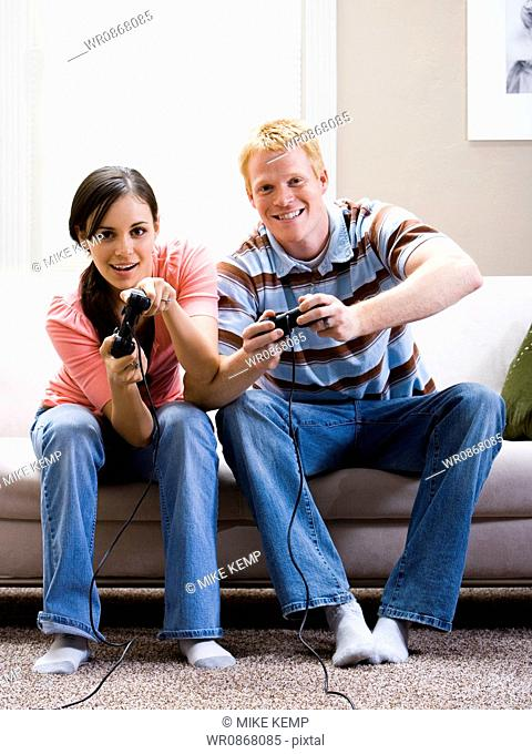 Man and woman sitting on sofa playing video games laughing