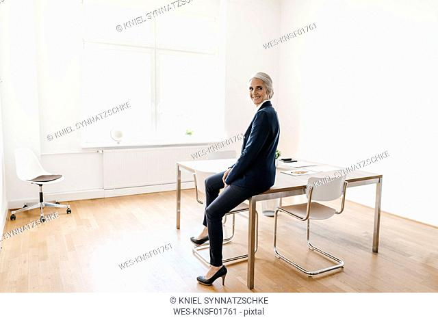 Smiling businesswoman sitting on table in office