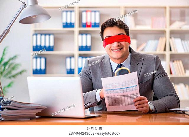 bddbfbe311a Blindfold businessman sitting at desk in office
