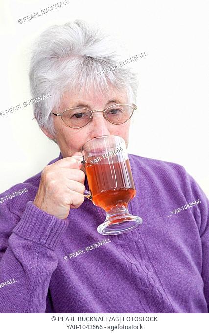 Britain UK Europe  Senior woman drinking red fruit tea in a glass mug MR 09/06