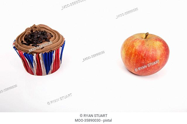 Fresh apple and chocolate cupcake against white background