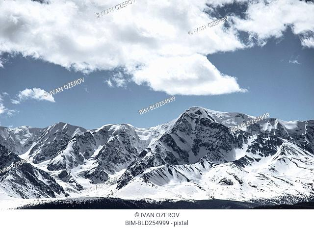 Clouds over snow covered mountains