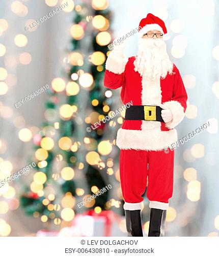 christmas, holidays, gesture and people concept - man in costume of santa claus pointing finger up over tree lights background