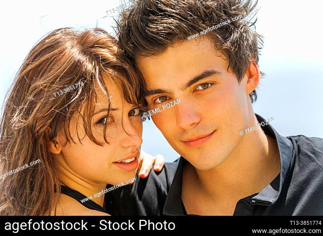 Young teenage couple portrait close-up both posing looking at camera