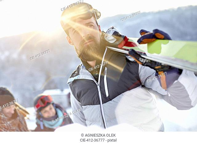 Male skier carrying skis in sunny field