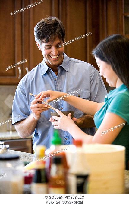 Asian girl showing Caucasian man how to use chopsticks