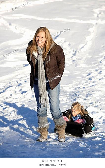 Mother pulling daughter up snowy hill on sled