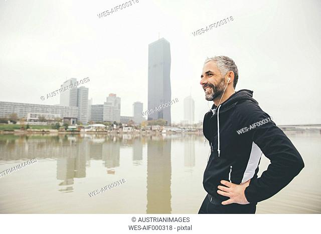 Austria, Vienna, portrait of smiling jogger with earphones in front of Donau City