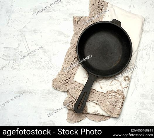 empty black round frying pan with handle, white table, top view