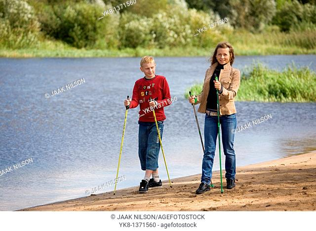 Young woman and teenage boy doing nordic walking by river water