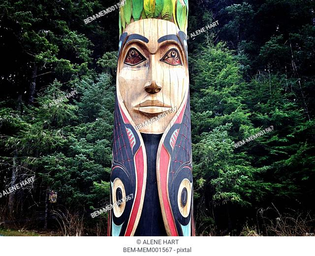 Ornate carved Native American totem pole in forest