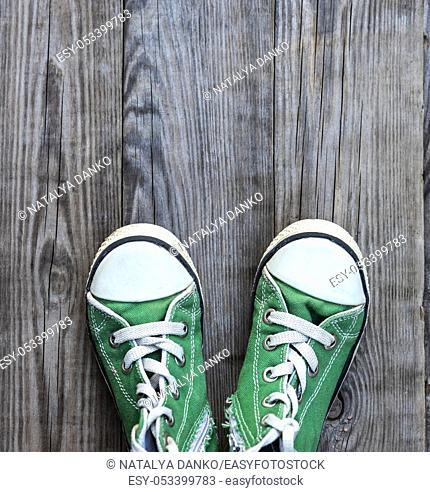pairs of old textile green classic sneakers stand on a gray wooden background, top view, copy space