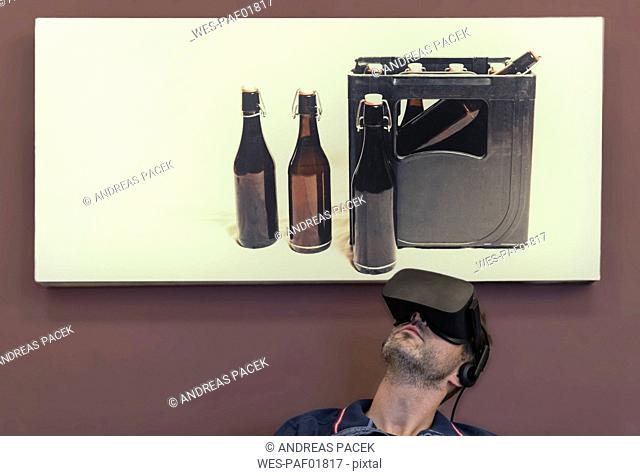 Man wearing VR glasses under photography of beer crate