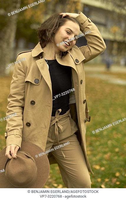 young playful woman walking outdoors in park during autumn season, ruffling hair, wearing coat, prankish, coquettish, smiling, flirtatious emotion