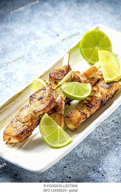 Grilled chicken breast skewers with lime on a light plate and light travertine marble table