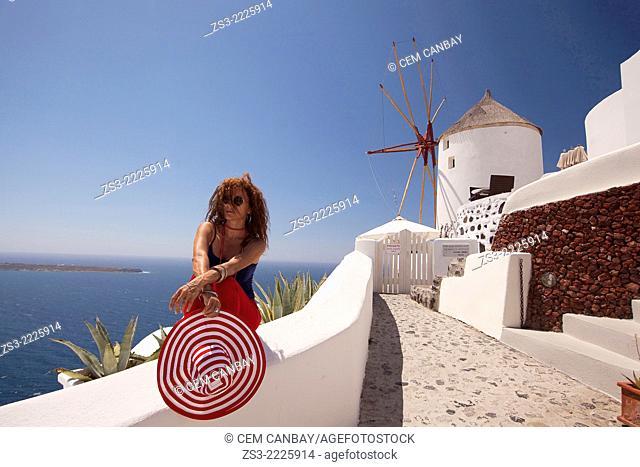 Woman sitting near a windmill, Oia town, Santorini, Cyclades Islands, Greek Islands, Greece, Europe