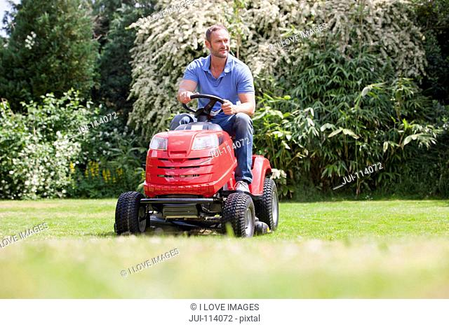 Man driving ride on mower, mowing grass in sunny summer yard