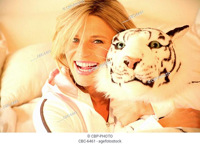 Portrait of Young Woman Relaxing at Home, Looking at Camera, Embracing Stuffed Tiger